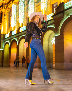 Winter lifestyle, young caucasian blonde model wearing jeans and a black jacket in the city illuminated for christmas at night