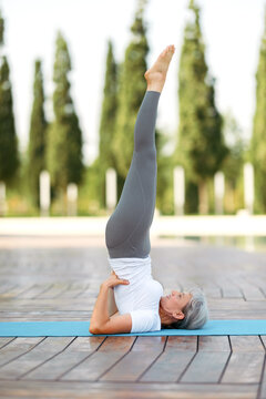 Mature woman in sports wear standing upside down in shoulderstand yoga pose outside on fresh air