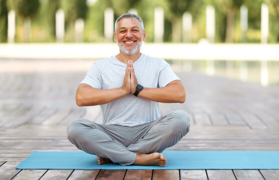 Calm happy mature man sitting in lotus pose on mat during morning meditation in park