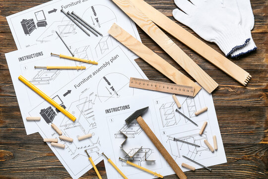 Furniture assembling plan, instructions and different tools on wooden background