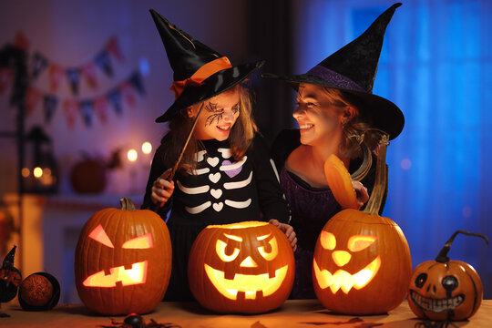 Happy family mother and little girl daughter in witch costumes celebrating Halloween at home