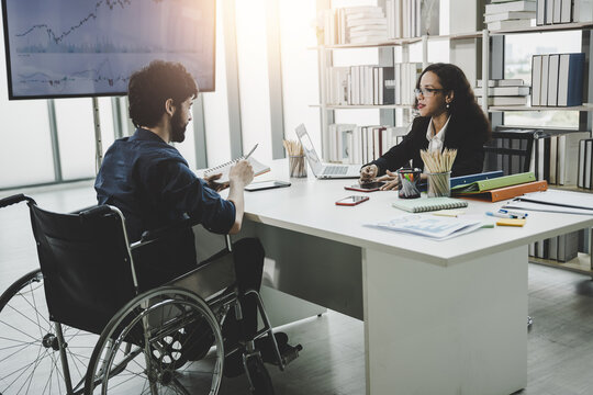 handicapped and disability business man sitting on wheelchair working planning with colleague normally equality and equal opportunity of human and teamwork concept