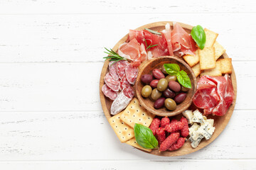 Obraz Antipasto board with prosciutto, salami, crackers, cheese, olives - fototapety do salonu