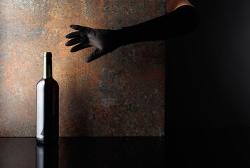 Fototapeta Woman hand in  glove reaches for a bottle of red wine. obraz