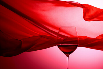 Fototapeta Glass of red wine on a background of waving red curtain. obraz