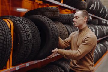 Fototapeta Man chooses winter car tires in the auto shop obraz