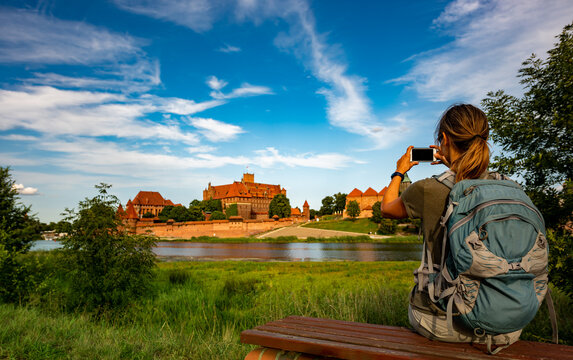 Tourist Backpacker woman takes picture of Malbork Castle