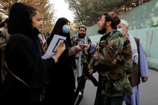Members of Taliban forces control people waiting to get visas, at the Iran embassy in Kabul