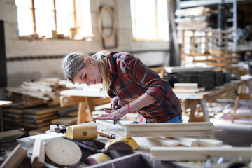 Fototapeta Portrait of female carpenter with goggles working on her product indoors in carpentry workshop. Small business concept. obraz