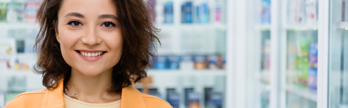 happy and tattooed woman smiling in drugstore, banner