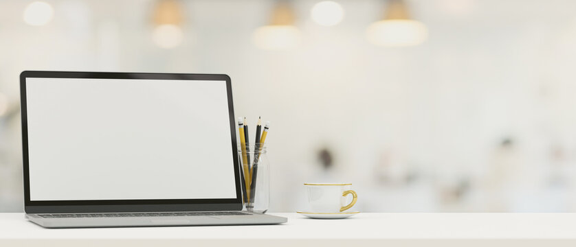 Laptop computer blank screen mockup on tabletop with copy space over blurred background