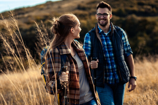 Couple with backpacks hiking together in nature on autumn day.