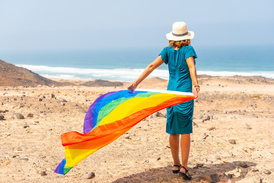 A lesbian person with a green dress, a white hat and with the LGBT flag by the sea, a symbol of homosexuality