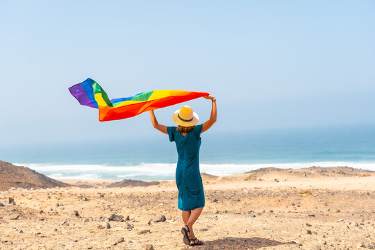 Lgbt symbol, a lesbian person with a green dress and a white hat with the rainbow flag by the sea, symbol of homosexuality