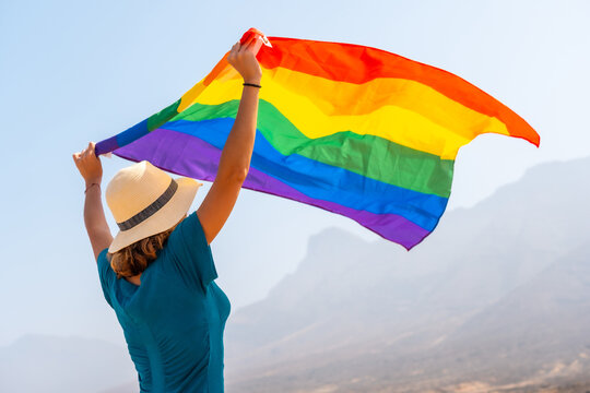 Lgbt symbol, a lesbian person in a green dress and a white hat with the rainbow flag in the desert