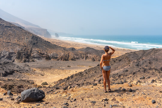 A young woman on a path of the wild beach Cofete of the natural park of Jandia, Barlovento coast, south of Fuerteventura, Canary Islands. Spain