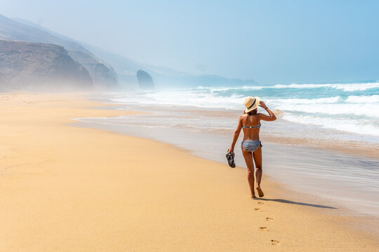 A young tourist walking alone on the wild beach Cofete in the natural park of Jandia, Barlovento coast, south of Fuerteventura, Canary Islands. Spain