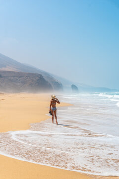 A young tourist with a hat walking alone on the Cofete beach of the Jandia natural park, Barlovento, south of Fuerteventura, Canary Islands. Spain