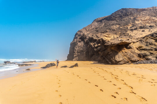 A young father in the Roque del Moro of the Cofete beach of the natural park of Jandia, Barlovento, south of Fuerteventura, Canary Islands. Spain