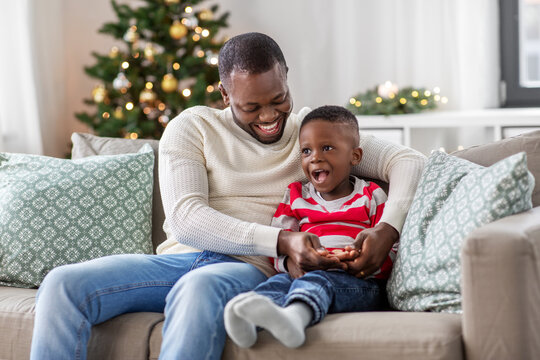 family, winter holidays and people concept - happy smiling african american father playing with baby son at home on christmas