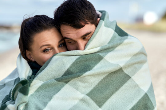 love, relationship and people concept - happy smiling couple in warm blanket on autumn beach