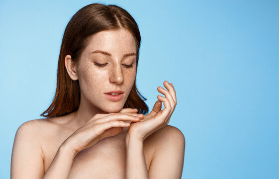 Skin care and women beauty. Young redhead woman with clean glowing facial skin, tenderly touching her palm and body after shower gel, standing over blue background