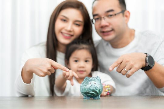 family savings, budget planning, children's pocket money.Asian family mother farther and daughter show piggy bank moneybox