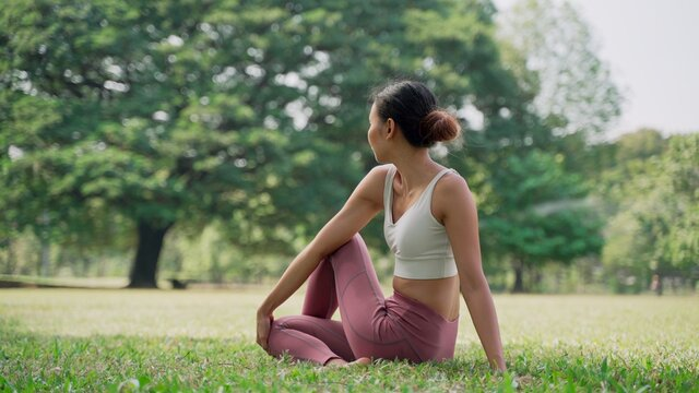 Asian young woman sitting on the grass in the HALF LORDS OF THE FISHES POSE outside in city park with the big trees background. Rearview of female practicing yoga outdoors on a sunny day.