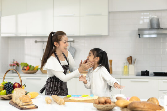 Happy asia family with daughter making dough preparing baking cookies, Daughter help parent preparing the bake Family concept