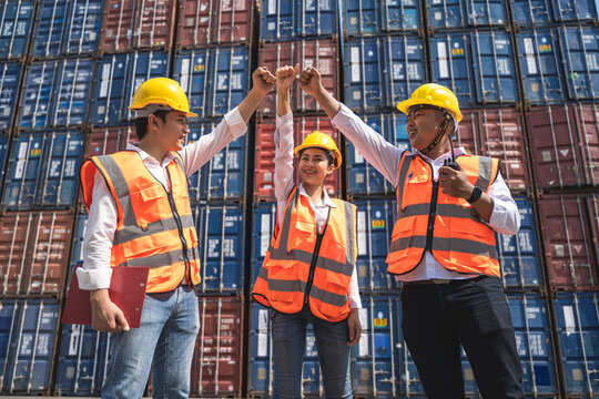 woman worker working with her colleague, standing with ware a yellow helmet to control loading and check a quality of containers from Cargo freight ship for import and export at shipyard or harbor