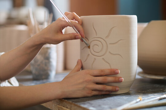 Close up of hands with a brush painting on a cup