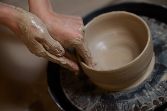 Close up of human hands making a bowl on a pottery wheel