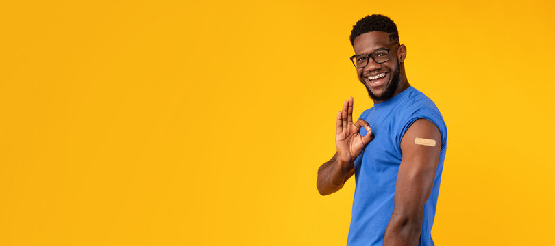 Vaccinated Black Guy Gesturing Okay Showing Arm, Yellow Background, Panorama