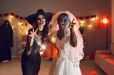 Portrait of two beautiful young women dressed up in spooky Wicked Witch and Dead Bride costumes...