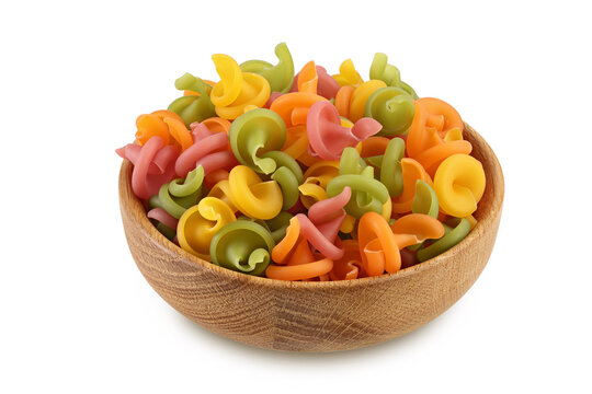 Raw colored pasta in wooden bowl isolated on white background with clipping path and full depth of field