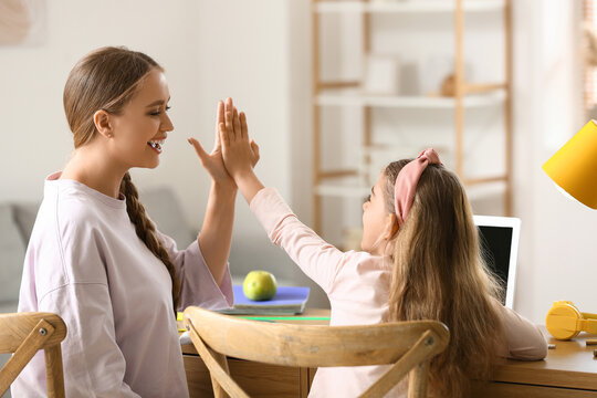 Little girl and her mother giving each other high-five at home