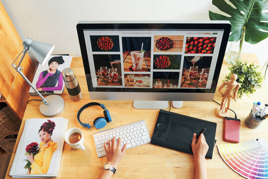 Directly above view of unrecognizable designer choosing photos for magazine page on modern computer in office