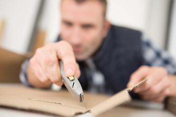 Obraz close view of cardboard being cut with a craft knife - fototapety do salonu