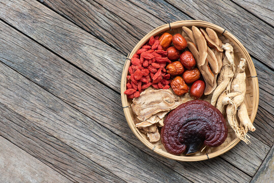 Ginseng, lingzhi mushroom, goji berry, red jujube and tea on  an old wooden background.top view,flat lay.