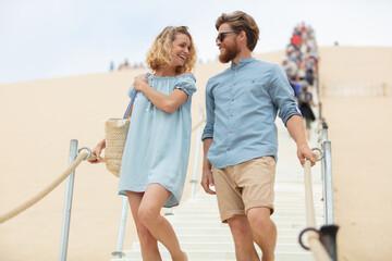 Fototapeta couple walking down the dune steps obraz