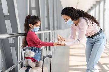 Fototapeta Travel Safety. Caring mom applying antibacterial spray on daughter's hands at airport obraz