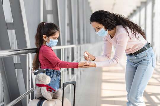 Travel Safety. Caring mom applying antibacterial spray on daughter's hands at airport
