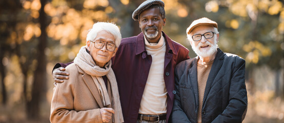 Fototapeta Elderly multicultural friends looking at camera during autumn outdoors, banner obraz