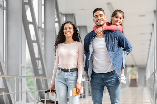Portrait Of Happy Loving Middle Eastern Family Walking With Suitcases In Airport