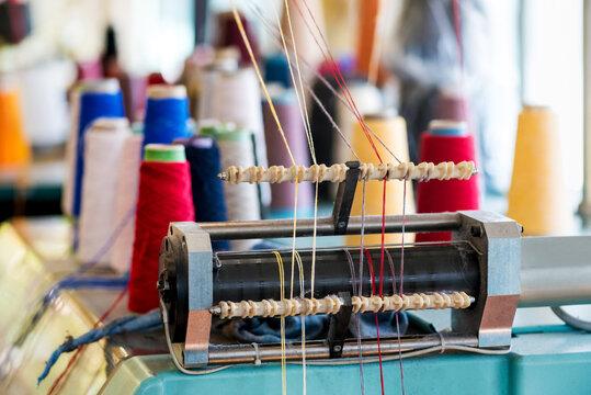 Yarn feeder with threaded wool on machine at a knitwear factory