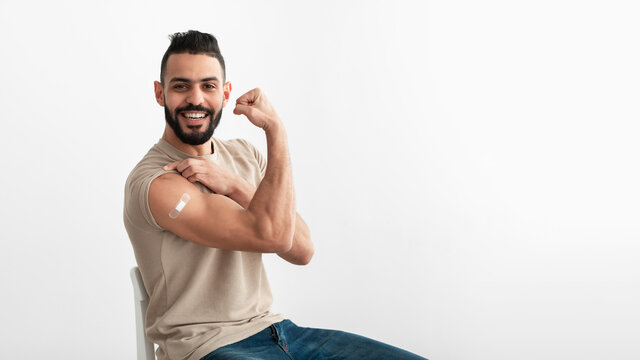 Vaccinated Arab man showing biceps muscle, demonstrating bandage after coronavirus vaccine injection on white background