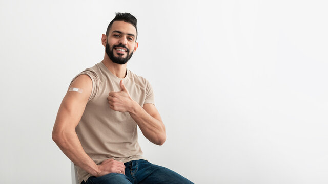 Arab man with adhesive band aid on shoulder after coronavirus vaccination showing thumb up gesture