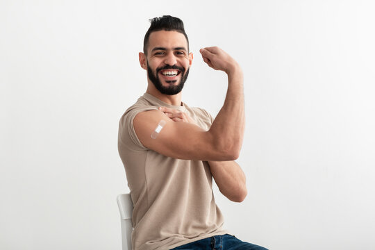 Young Arab man with adhesive bandage getting vaccinated against covid-19, demonstrating his muscles on white background