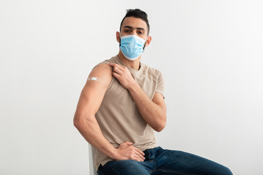Vaccinated Arab man in face mask showing arm with band aid after covid-19 vaccine shot on white studio background