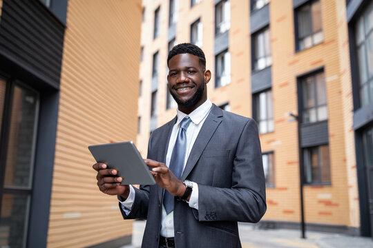 Happy african american company employee working with tablet computer during lunch break outdoors, free space